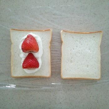 ラップを敷いた上に食パン、生クリーム、洗って水気を切ったフルーツを置きます。大きめのフルーツを使うことで、より見栄え良く仕上がりますよ。