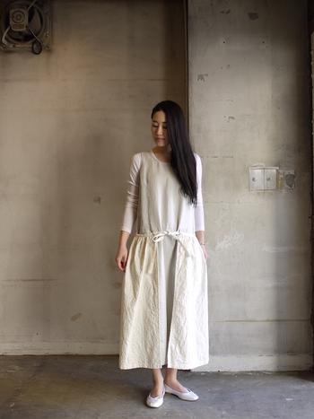 リネンワンピースにコットンのエプロンを重ねたデザインが光る個性的な一枚。白のバレエシューズを合わせて、大人の可憐ささと質感のグラデーションを楽しんで。