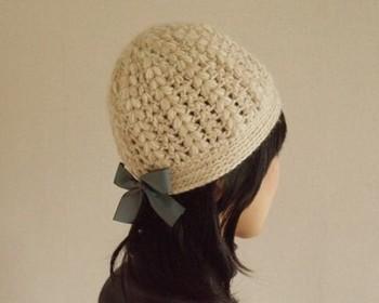 カギ針で二本どりで編んだ、ふんわりガーリーな帽子。後ろについた青いリボンがクラシカルな雰囲気です。