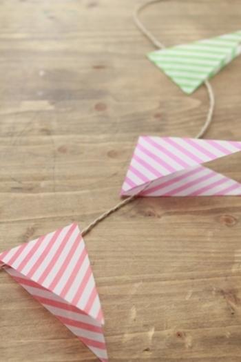 可愛い柄の折り紙を手に入れたら、三角形に折って切り取り、ガーランドに。こちらはダイソーのトレペタイプのちよがみだそうです。