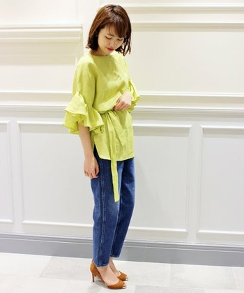 イエローグリーンが色鮮やかなフレアスリーブブラウス。スリムシルエットのデニム&ヒールでレディライクな着こなしに。