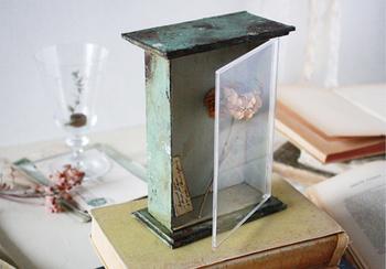 100均DIYのアンティーク調ケースとさりげなく飾られたグラスの相反する輝きがフェイクグリーンを引き立て合っています。