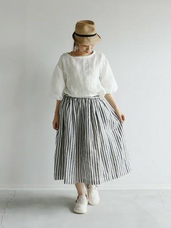白のトップスとストライプ柄のギャザースカートを合わせた清潔感溢れるコーディネート。夏はコットンやリネンなどの涼しげな素材を選ぶと、爽やかでナチュラルな雰囲気になります。
