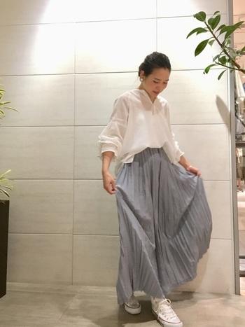 ゆるっとしたサイズ感のブラウスに、ロングプリーツスカートを合わせた大人フェミニンスタイル。髪はアップスタイル、足元はホワイトのコンバースにして軽やかに。