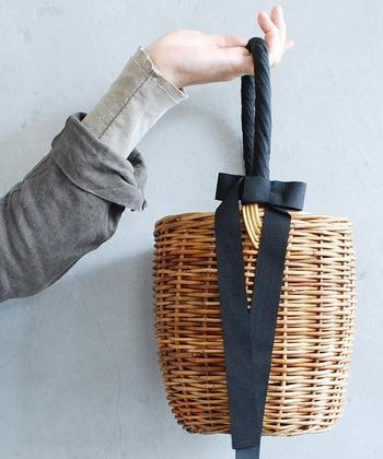 安定感のある樽型のしっかりとした本体に、長く垂れた黒のグログランリボンがアクセントになったバッグ。内布が張られていて巾着のようにして縛り持ち歩けるので、中身がオープンになる心配がありません。