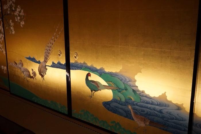 復元された「桜花雉子図」です。原図は狩野派絵師による作だったそうです。金色に輝く襖絵には、桜の木の下で遊ぶ雉(きじ)の親子が微笑ましく描かれています。