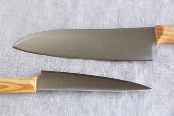"""出番の多い""""三徳包丁""""は、背の厚みがしっかりとしていて、大きな野菜でもザクザクと楽に切ることができます。ハンドル部分に使われているのは""""オリーブの木""""。きれいな木目としっくりと手に馴染むフォルムがいいですね。普段のお料理がもっと楽しくなりそうな包丁です。"""