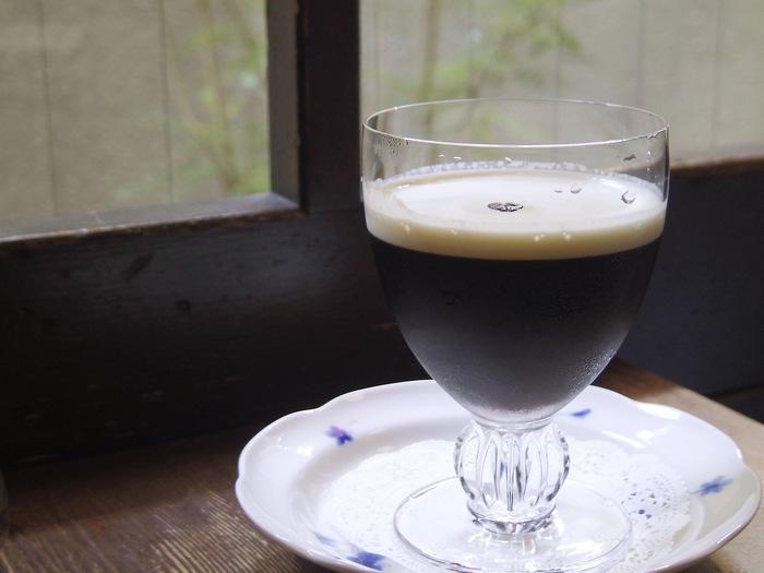 ワイングラスに入れられた「琥珀の女王」。アイスコーヒーの上に生クリームが注がれ、コーヒー豆がトッピングされています。すっきりとした甘味でコクがあります。