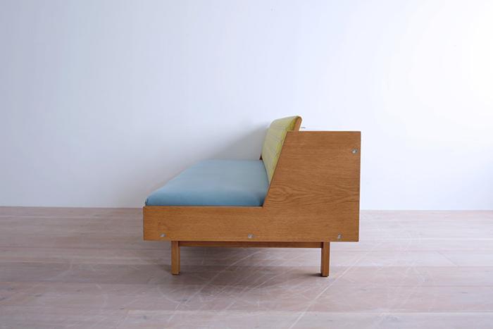 もともと、デンマークで寄宿舎のために設計されたソファ。背もたれの後ろにある箱状になった部分に秘密があるんです。箱状の部分の蓋を上げて、背もたれを持ち上げると…。