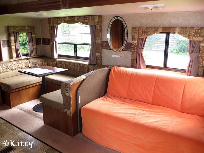 落ち着いた内装のトレーラーハウスはエアコンつきで、季節を問わず快適にすごせます。シャワールームや大きなベッド、翌日の朝食を用意できるキッチンなどが揃います。