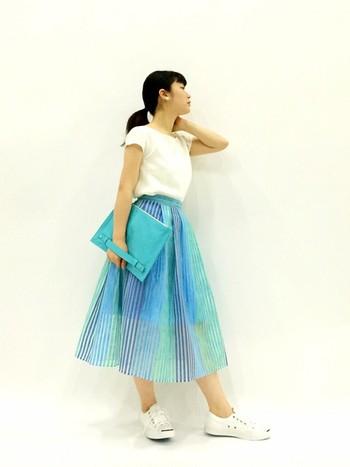 ターコイズブルーのグラデーションが美しい、夏らしい爽やかなスカートスタイル。シアーなストライプ柄が涼しげな印象です。