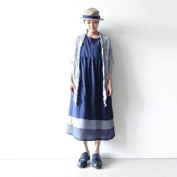 洗いざらしの風合いが魅力のネイビーブルーのワンピース。裾のパネルボーダーがハットのリボンとマッチした、統一感のあるコーディネートです。