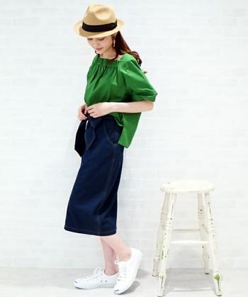 鮮やかな緑色のブラウスとデニムスカートのコーディネート。濃紺デニムと合わせると落ち着いた印象になります。ストローハットと白のスニーカーで軽さと季節感をプラスして。