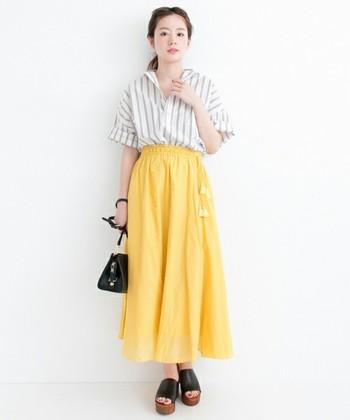 清潔感のあるストライプシャツを抜き襟に。イエローのスカートと組み合わせて、夏のフレッシュなコーディネートに仕上げています。