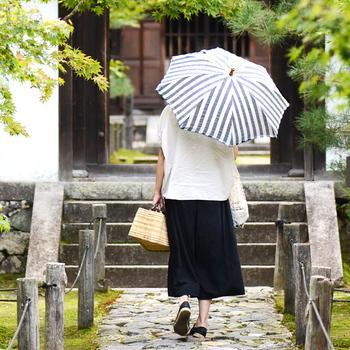【SUR MER(シュールメール) | リネンリゾートストライプ 日傘】  ボーダー柄が爽やかなSUR MERの長傘タイプの日傘。素材はリネンで、持ち手は天然の竹を使用し、職人さんの手で大切に作られています。紫外線防止加工が施され、リネンの耳のフリンジがワンポイントに。