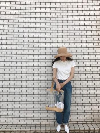 女優のようなツバ広帽も麦わら帽子なら取り入れやすい。シースルーバッグと白のサンダルでデニムのカジュアルスタイルもちょっぴり大人っぽく。