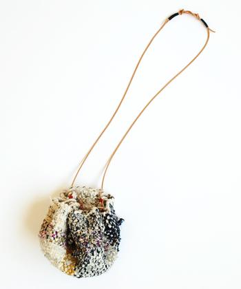 小さめサイズの裂き編みでつくられたlente(レンテ)の巾着バッグ。コロンとしたシルエットで、ほっこり感漂う可愛らしいデザインです。ショルダーや手提げとしてだけでなくインテリアなどにも活用できそう。