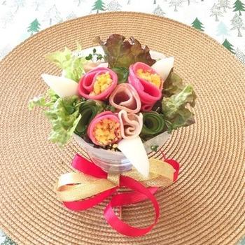 花束サラダをペーパーでくるんでから、円すい状のグラスに入れています。赤い具材は、紅芯大根。ゆで卵の黄身をほぐしてお花の中心にあしらうなど、素敵なアイデアがいっぱいのブーケサラダです。レタスのほかに繊細なブロッコリースプラウトを使って、変化をつけていますね。