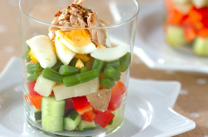 キューブにした数種類の野菜を順にグラスに重ねていき、サラダの基本「ヴィネグレットソース」をかけます。写真のような円柱で模様のない、シンプルなグラスがあるといいですね。