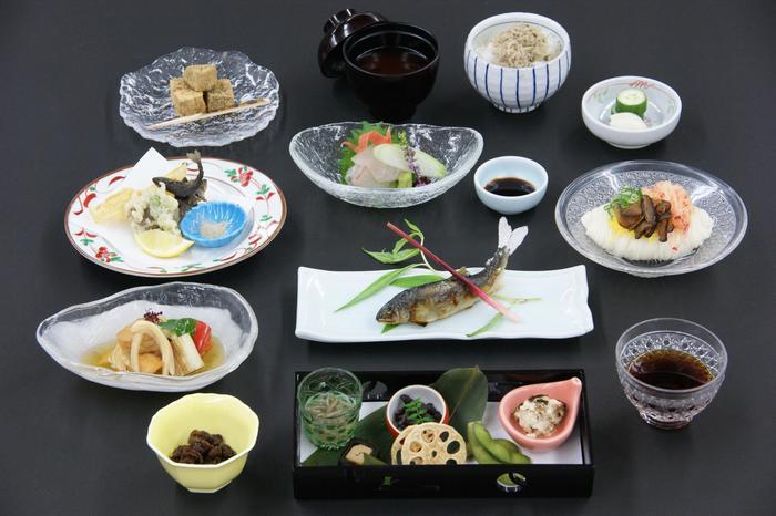 「お昼のおまかせ会席」。鮎や湯葉など様々な京の味を堪能できます。猪肉をこんにゃくで巻いた天麩羅、なんてものも!器も涼しげなものが選ばれていますね。