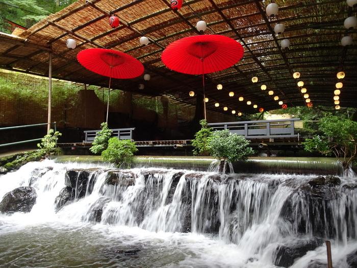 木々を超えて滝のように流れる水が清涼感をくれます。朱塗りの和傘が風情を添えますね。
