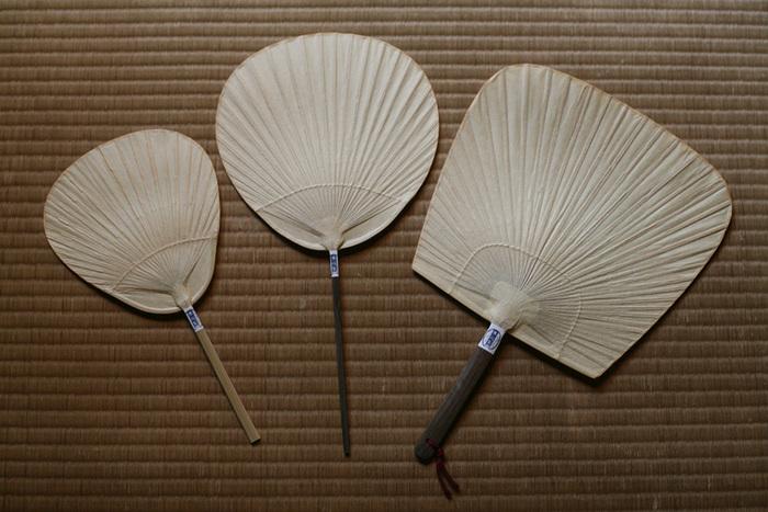 """竹骨に紙を張った現在のうちわの形は、室町時代には既にあったと言われています。 栗川商店は、京都・丸亀に並んで、日本のうちわ産地として名高い熊本・来民町の製法を受け継いでいます。渋うちわは、渋柿をうちわに塗ることにより、和紙を丈夫に長持ちさせ、防虫効果の役目を果たします。来民のうちわは""""民が来る""""とことから商売が繁盛するとされ、縁起物・贈り物としても使われてきました。 栗川商店の渋うちわ/職人.com"""