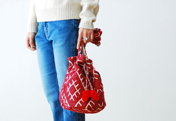 ジャガードオルテガファブリックで作られたBINDU(ビンドゥー)の巾着バッグ。鮮やかな赤が可愛らしく、コーデに花を添えてくれます。アクセントとなっているタッセルも可愛いですね。