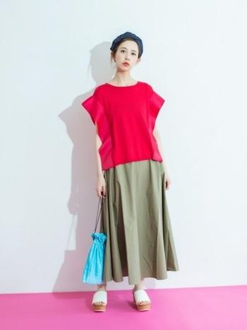 赤のトップスとカーキのスカートに涼しげな水色の巾着バックを。色んな色を取り入れながらもバランスの取れたこなれ感のある夏コーデです。