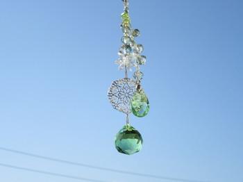 爽やかなグリーンのクリスタルガラスを使ったサンキャッチャーです。太陽の光を受けて輝きを放ち、虹のような光のカケラを作り出します。窓辺の光が当たる場所に吊るして、涼しげにきらきらと輝くガラスを見ていると、気持ちも穏やかになりそうですね。