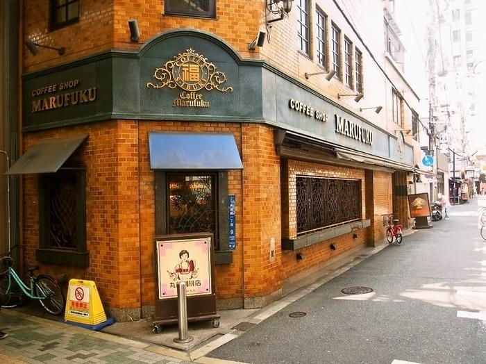"""平成2年に完成した千日前の丸福本社ビルは、1・2階が店舗になっています。創業時は大阪のディープスポット""""新世界""""に、戦後は""""千日前""""に店を構え、さらに平成時代に入ってから瓶詰珈琲が販売されるようになりました。  今では、東京、神奈川、福岡など、全国に約30ほど店舗があります。"""