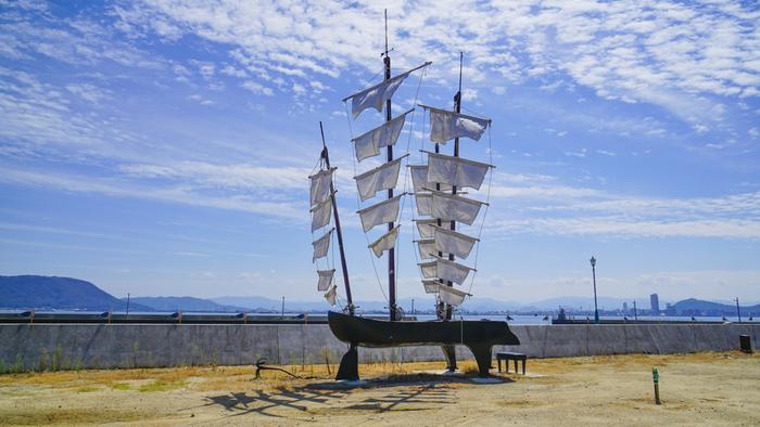 カモメの駐車場を横目に歩いて行くと見えてくるのが、『20世紀の回想』。海を背景にグランドピアノとその上に立つ4本の帆が印象的な作品です。