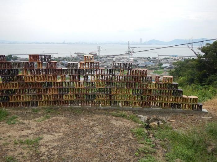 かつて段々畑だった傾斜地に約400個の陶のブロックを設置した作品、「段々の風」。 町並みと海が見渡せる光景と作品の一体化を図り、大パノラマの景観を見せてくれます。