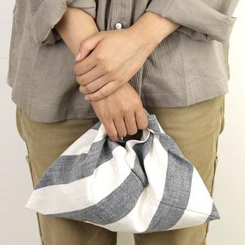 アースカラーのコーディネートに、ベーシックな配色の「あづまバッグ」がポイントに。新潟県の伝統柄「亀田縞」というデザインなのだそう!