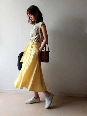 花柄ブラウスとイエローのスカートを合わせたフェミニンスタイル。程よくカジュアル感をプラスしてくれる白スニーカーは、甘めのコーデもバランスよく着こなせます。