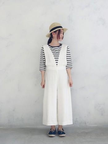 白のワイドサロペット×ボーダーの爽やかなマリンスタイル。麻ひもがポイントのブルーのエスパドリーユと麦藁帽子が、コーディネートにナチュラルな季節感をプラスしています。
