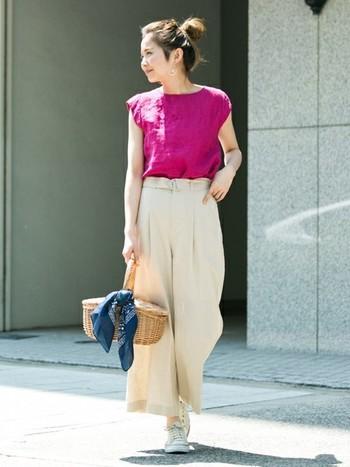 ビビッドカラーが印象的なパンツスタイルには、かごバッグにバンダナスカーフを巻きつけるとバランスが取れ華やかな印象に。