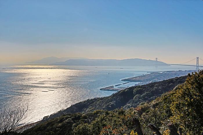 回転展望台からは360℃のパノラマで景色を見渡すことができます。こちらは明石・淡路島方面の景色。穏やかな瀬戸内海と明石海峡大橋、六甲山の木々が目を癒しの時間をくれます。