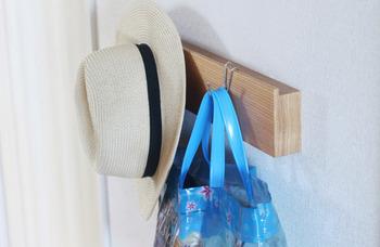 """帽子やバッグなど、お出かけ用のアイテムは玄関近くに吊るして収納して。「あっ、忘れた!」という時にも慌てずに持っていける、""""忘れ物を減らす""""収納術です。  玄関にS字フックをかけられる場所が無い場合は、無印良品の「壁に付けられる家具(長押)」を使っても。壁が石膏ボードなら簡単に設置できます。穴も小さめなので、賃貸の方にもおすすめ。"""