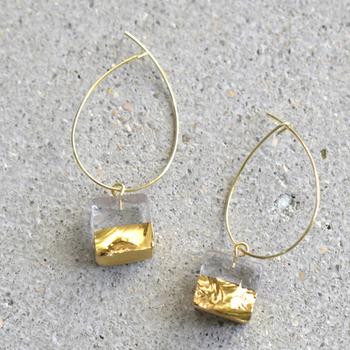 sorte(ソルテ)ガラス×ゴールドフープピアスは、ガラスを棒状に伸ばして金太郎飴のようにカットし、断面のいびつさをデザインとして残したまま、滑らかに磨き上げて作られています。モチーフの半分に施された金箔がとても華やかです。