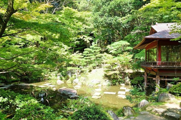 「池泉回遊式庭園」の日本庭園。池の周りを回りながら、木々や池の景色を楽しむことができます。 画像の右手は、当時茶室だった「真珠亭」。朱塗りの建物が庭園に華やかさを添えています。