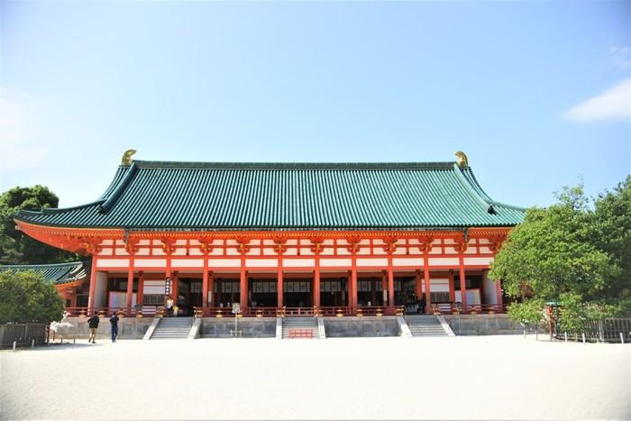 平安神宮は、平安遷都1100年祭(1895年・明治28)に、京都の町おこし事業の集大成として創建されました。平安遷都を行った桓武天皇と、平安京最後の天皇である孝明両天皇を祀っています。平安京が開かれら当時の8分の5サイズに再現された社殿は、鮮やかな朱色と緑に塗りわけられ壮麗な佇まいで、国の重要文化財にも指定されています。 縁結びの神様としても有名で、他にも、商売繁盛・学業成就・開運招福などのご利益もあるそうです。