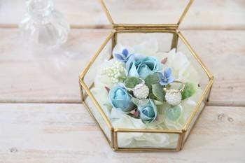お花と一緒にアクセサリーをガラスケースの中に飾るアイデア。リングピローのように、お花の上にリングを乗せれば、こんなにエレガントに♪