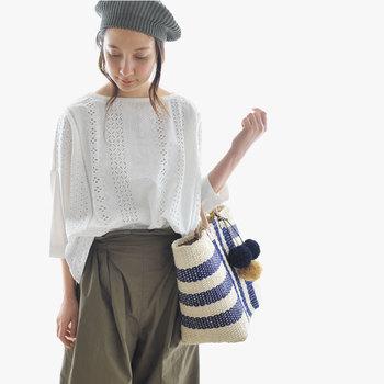 丈夫なラフィア製のトートバッグ。細めで持ちやすい牛革のハンドルは上質な印象。かごバッグ本体と同じ素材のポンポンチャームは、ふさふさ感がまた可愛い◎ 他のかごバッグと差をつけられるデザインです。