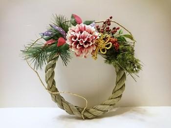 大ぶりなダリアの花が印象的なしめ縄リースです。 現代風のアレンジですが、藁縄・松・南天などお正月飾りの本来の素材を使っているので、正統派の厳かな雰囲気を醸し出しています。