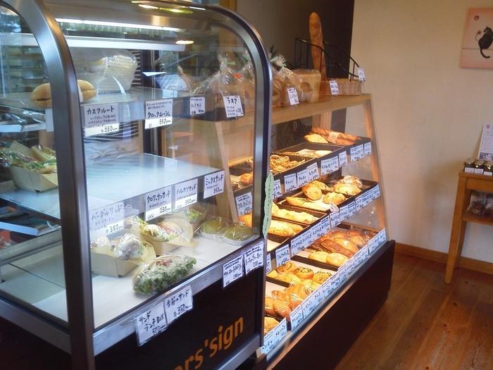 ナチュラルな雰囲気の店内のショーケースに並んだ天然酵母パンの数々。塩パンやクロワッサンの他に惣菜系のパンや菓子パンまで揃っています。ベイカーズサインはパンだけでなく、サンドイッチが充実しているのも魅力。