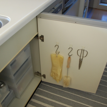 これは、驚きの活用法!シンク下の扉裏も見逃しません。100均ショップなどで売っているフックに「S字フック」をかけて。キッチンばさみやブラシ、ゴム手袋を吊るします。  ゴム手袋は洗濯ばさみで挟んでから、フックにかければOK。もちろん、無印良品の「ワイヤークリップ」でも◎  このアイデアは、キッチン以外に洗面台下や玄関のシューズボックスの扉裏でも活用できそうですね。