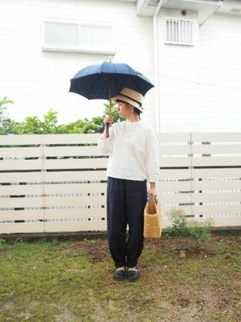 白いブラウスにバルーンシルエットのパンツ。シンプルナチュラルなコーデに、帽子と日傘で日よけ対策はバッチリ。小物使いで可愛らしく。