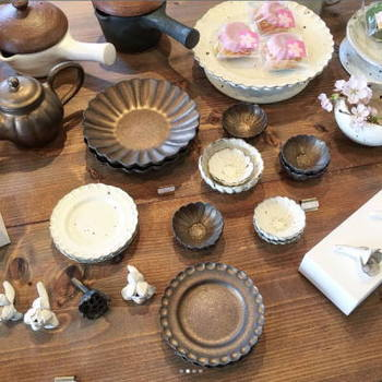 マーガレットのような縁取りが可愛らしいデザインの器。素朴な風合いの白い器と、錆のような渋い味わいのある器。テーブルを存在感たっぷりに彩ってくれそう。