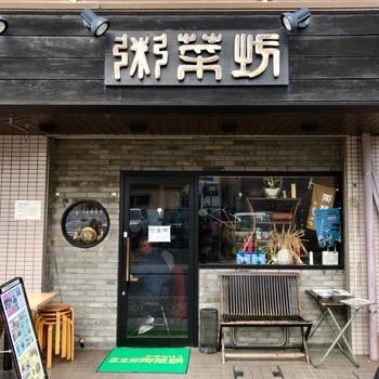 モダンな雰囲気の外観ですが、看板の「粥菜坊」の文字は中国古代の篆書を銅で作成し、中国の古建造物に見られるグレーの古レンガを取り寄せ、中国らしさにこだわっています。時間の経過とともに味わいを増していきますね。