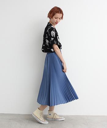 シンプルなモノトーンのアロハシャツには、幅の違うラインがひとクセあるプリーツスカートを合わせて。足元はコンバースでカジュアルに。